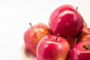 光が当たってつやつやなりんごの画像